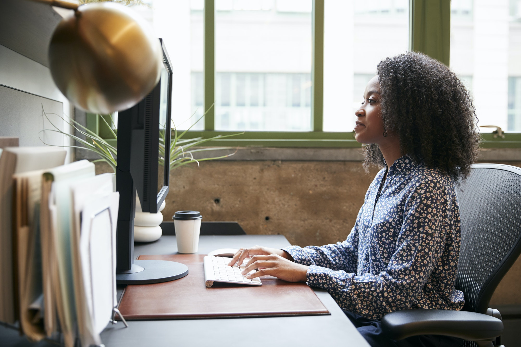 Black woman working at a computer in an office, side view