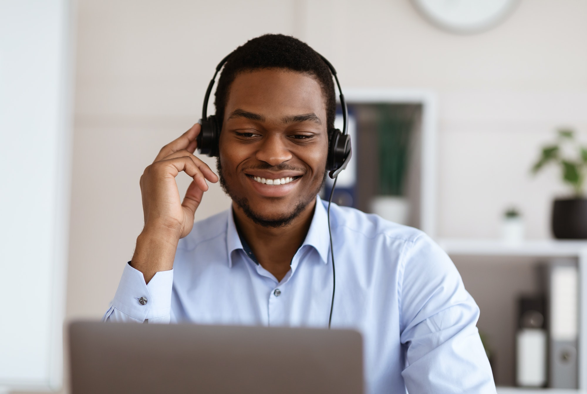 Closeup of black worker with headset using laptop, office interior