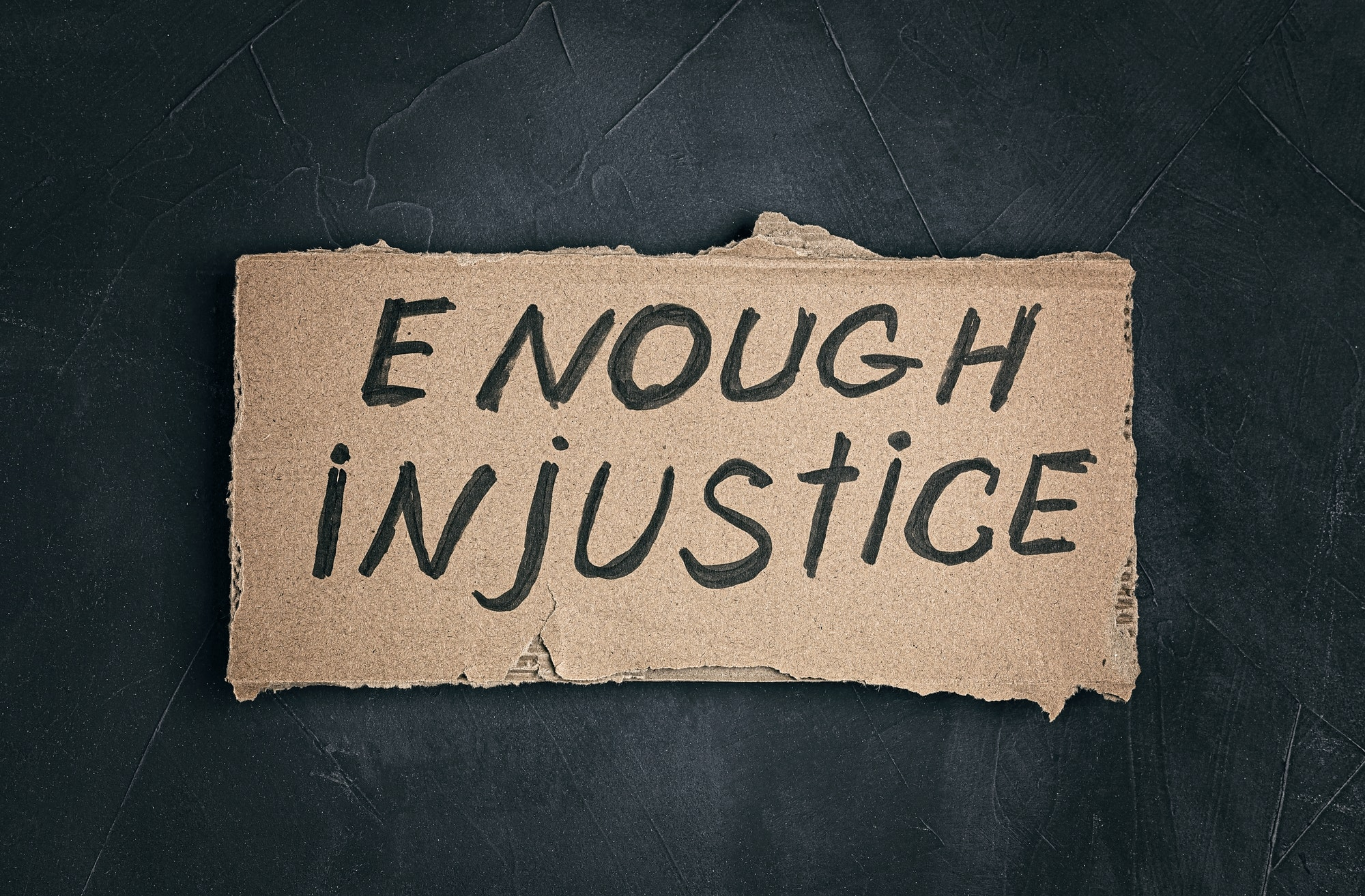 Enough injustice text on cardboard on dark background