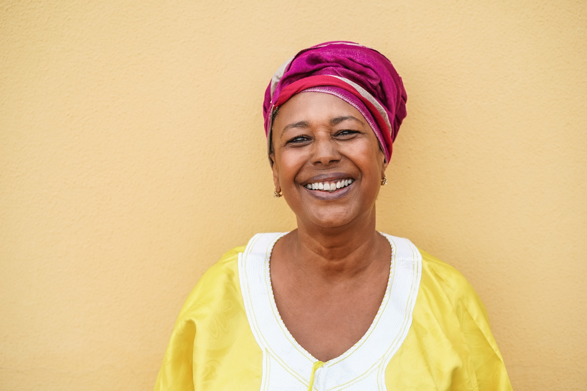 Happy senior african woman wearing traditional dress looking at camera