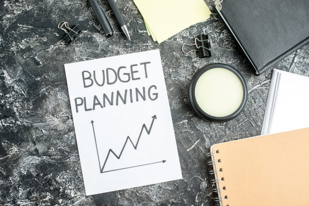 top view budget planning note with pens and copybooks on gray background job copybook school student
